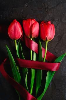 Czerwona wiązka tulipanowi kwiaty z czerwonym faborkiem na textured czarnym tle, odgórnego widoku kopii przestrzeń