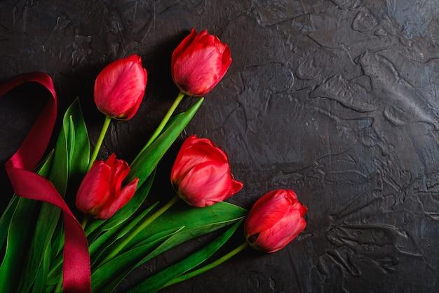 Czerwona wiązka tulipanowi kwiaty z czerwonym faborkiem na textured czerni ścianie, odgórnego widoku kopii przestrzeń