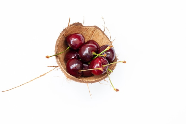 Czerwona wiśnia w łupinach orzecha kokosowego, na białym tle.