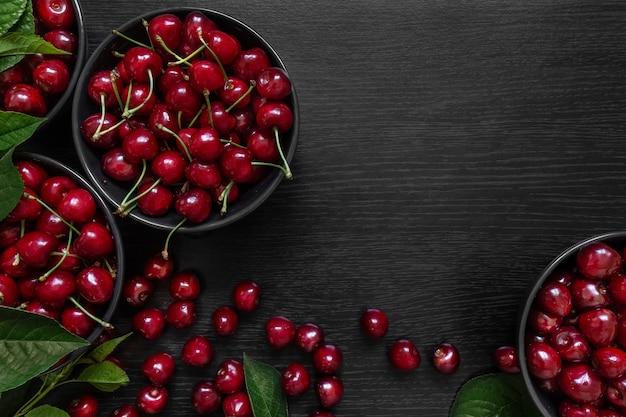 Czerwona wiśnia z zielonymi liśćmi w ciemnym talerzu na czarnym stole, tło, tekstura
