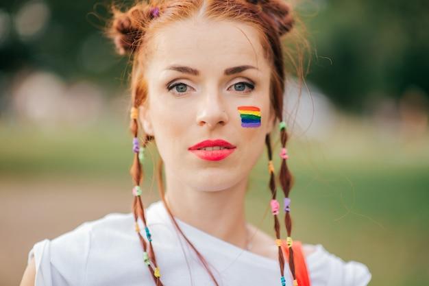 Czerwona włosiana dziewczyna z lgbt homoseksualnej dumy flaga na jej twarzy zbliżenia portrecie.