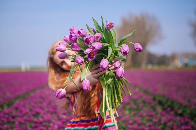 Czerwona włosiana kobieta jest ubranym suknię trzyma kosz z bukietem tulipanów kwiaty