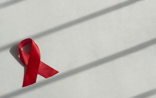 Czerwona wstążka do pomocy i koncepcji świadomości dnia hiv na niebieskim sztandarze z miejscem na kopię tekstu