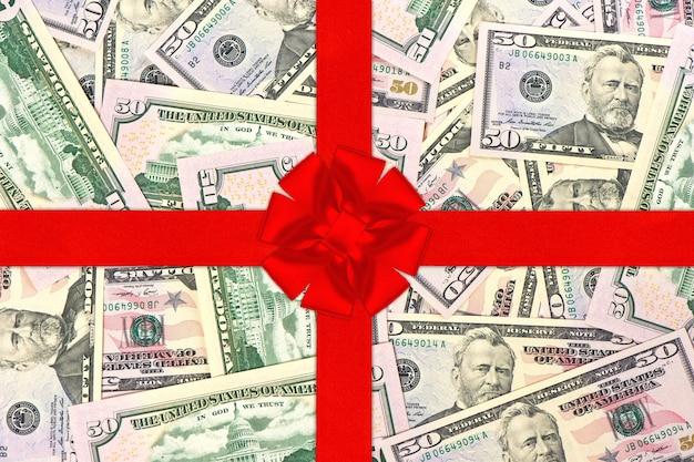 Czerwona wstążka prezentowa z kokardą nad dolarami amerykańskimi pieniądze tło zakupy koncepcja karty podarunkowej