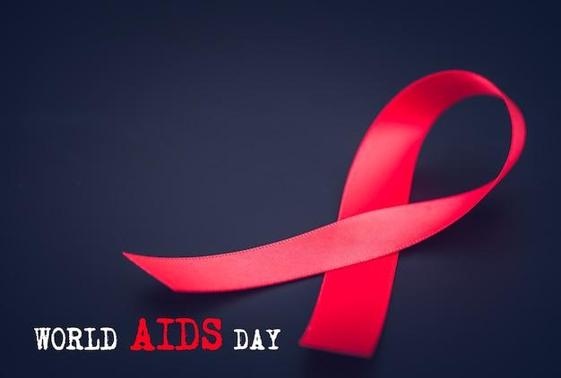 Czerwona wstążka świadomości na czarnym tle na kampanię world aids dnia