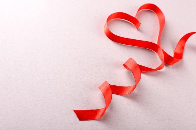Czerwona wstążka w kształcie serca na jasnym tle z teksturą
