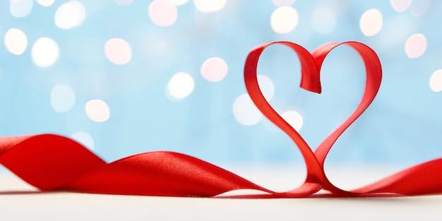 Czerwona wstążka w kształcie serca na niebieskim tle. karta walentynki