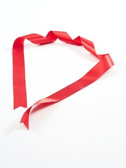 Czerwona wstążka wygięta na białym tle