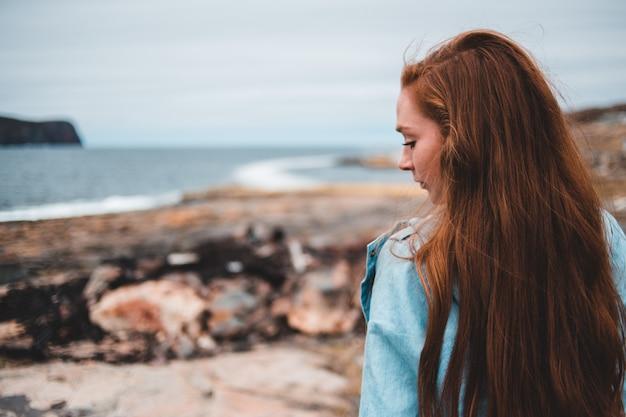 Czerwona z włosami kobieta przez zbiornik wodny