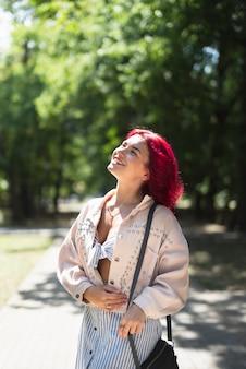 Czerwona z włosami kobieta w parku