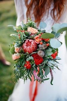 Czerwona z włosami panna młoda trzyma perfect ślubnego bukiet robić czerwień