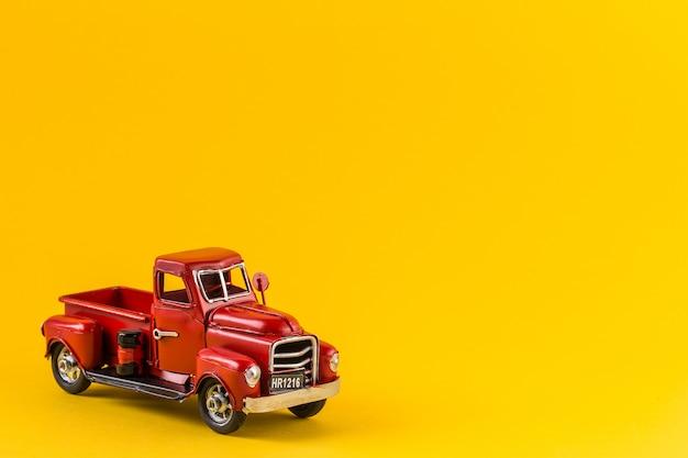 Czerwona zabawka ciężarówka na jasny żółty