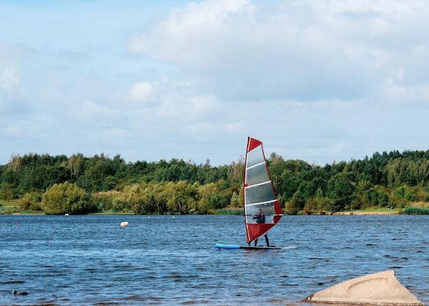 Czerwona żaglówka na jeziorze