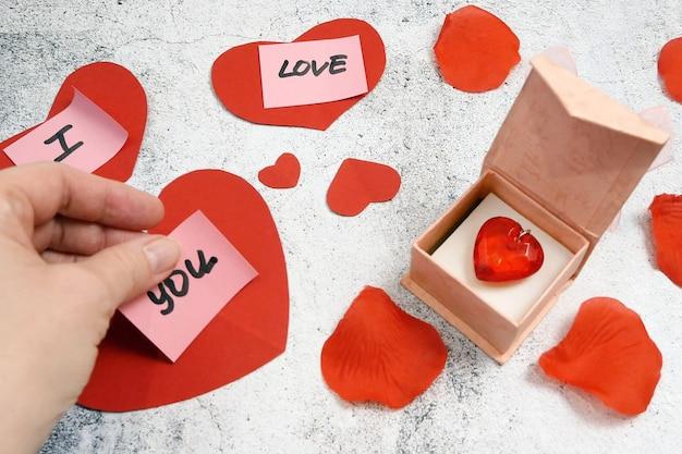 Czerwona zawieszka w kształcie serca w ozdobnym pudełku i czerwone papierowe serce z naklejkami o miłości