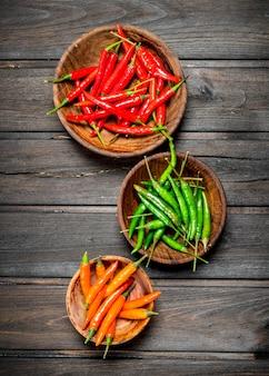 Czerwona, zielona, pomarańczowa papryka w misce na czarnym rustykalnym stole