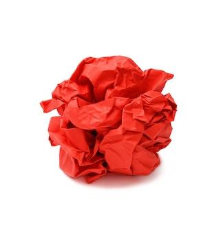 Czerwona zmięta kulka papieru na białym tle na białej powierzchni, jeden kawałek