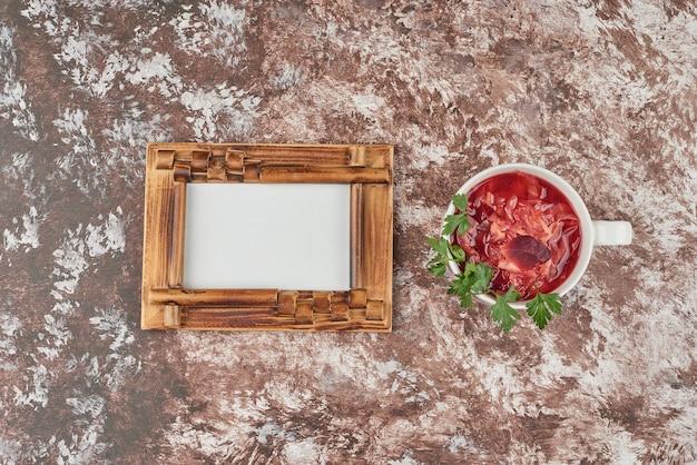 Czerwona zupa jarzynowa w białym kubku z ziołami.