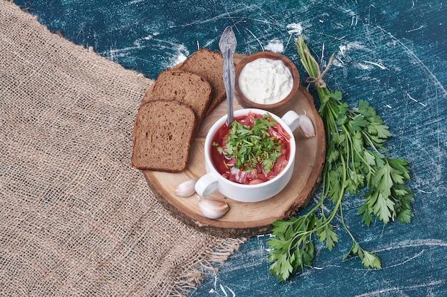 Czerwona zupa z ziołami i kromkami chleba.