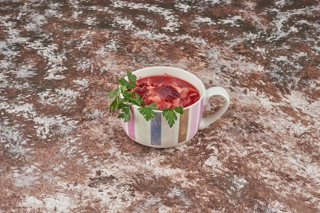 Czerwona zupa z ziołami podawana w białej filiżance.