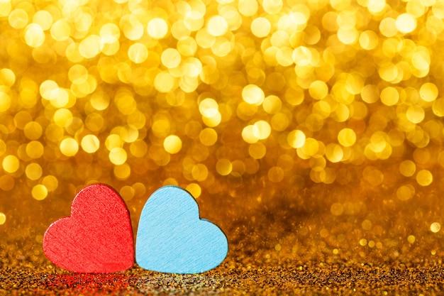 Czerwone abd niebieskie małe ozdobne serca na tle złoto żółtego blasku brokatu z niesamowitymi światłami bokeh. miłość lub romantyczna koncepcja walentynki. tło wakacje.
