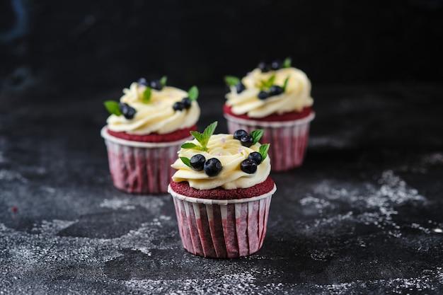 Czerwone aksamitne babeczki z kremem serowym. deser przyozdobiony świeżymi jagodami i miętą.
