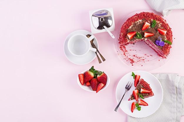 Czerwone aksamitne ciasto na różowym stole. picie herbaty ustawienie stołu widok z góry