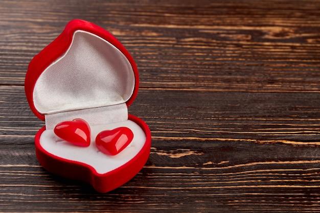 Czerwone aksamitne pudełko z kolczykami w kształcie serca. pudełko w kształcie serca z dwoma małymi serduszkami i miejscem na kopię. szczęśliwych walentynek.
