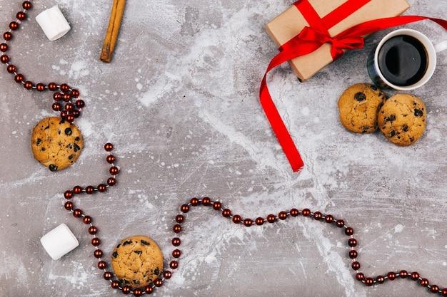 Czerwone białe cukierki, ciasteczka, ptasie mleczko, filiżanka kawy i obecne pudełko leżą na szarej podłodze