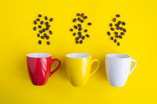 Czerwone, białe, żółte filiżanki i ziarna kawy na żółto