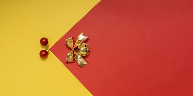 Czerwone bombki i złoty dzwonek z kokardą na tle żółtoczerwonych dekoracji sylwestrowych