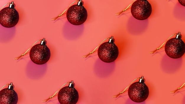 Czerwone bombki w rzędach na różowym świątecznym tle