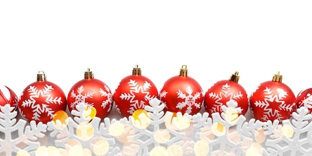 Czerwone bombki z płatki śniegu i złote światła na białym tle