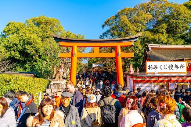 Czerwone bramy torii w fushimi inari taisha z turystami