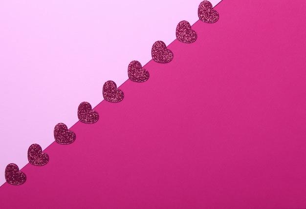 Czerwone brokat serca na różowym i czerwonym tle. romantyczne, koncepcja walentynki. widok z góry.