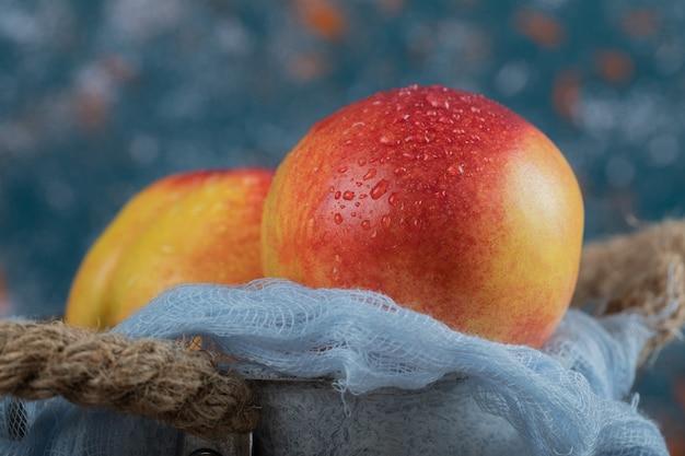 Czerwone brzoskwinie na białym tle na niebieski ręcznik kuchenny
