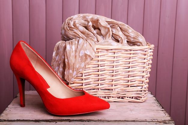 Czerwone buty damskie i szalik na ławce na drewnianym tle