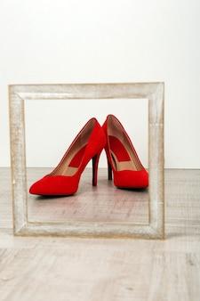 Czerwone buty damskie z ramą na podłodze