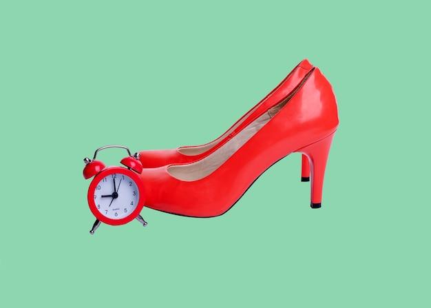 Czerwone buty i alarm na zielonym tle