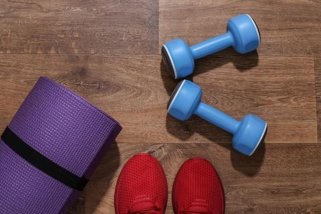 Czerwone buty sportowe, hantle, gumki fitness, mata na drewnianej podłodze. koncepcja treningu.