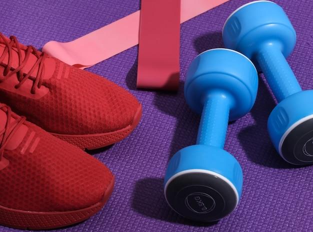 Czerwone buty sportowe, hantle, gumki fitness na fioletowej macie sportowej. koncepcja treningu.
