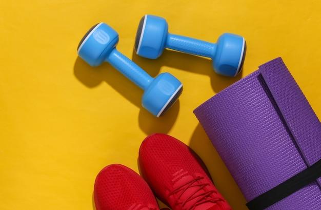 Czerwone buty sportowe, hantle i mata do jogi na żółtym jasnym tle z głębokim cieniem. skład fitness. leżał płasko.