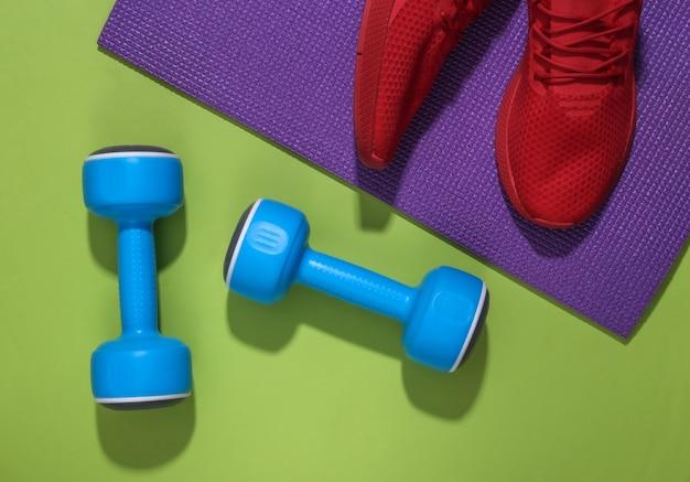 Czerwone buty sportowe, hantle i mata fitness na zielonym tle. koncepcja treningu.