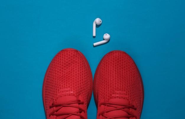 Czerwone buty sportowe i bezprzewodowe słuchawki na niebieskim tle. akcesoria sportowe.