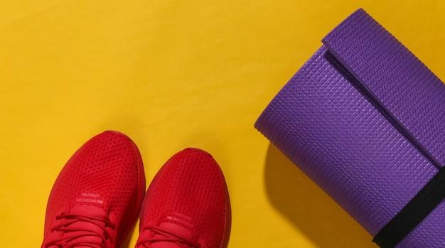 Czerwone buty sportowe i mata do jogi na żółtym jasnym tle z głębokim cieniem. skład fitness.