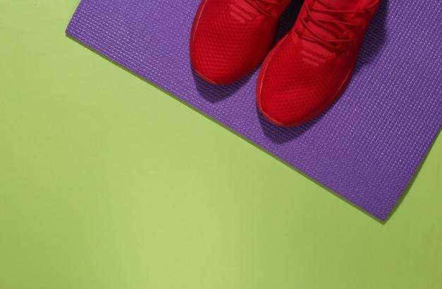 Czerwone buty sportowe i mata fitness na zielonym tle. koncepcja treningu. skopiuj miejsce