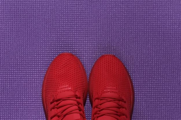 Czerwone buty sportowe na fioletowej macie sportowej. koncepcja treningu.