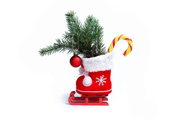 Czerwone buty świąteczne z lizakiem prezenty i czerwoną bombką na świątecznych saniach
