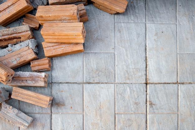 Czerwone cegły na cementowej podłodze w budowie. widok z góry