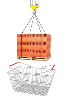 Czerwone cegły na drewnianej palecie z koszykiem na zakupy w supermarkecie na białym tle