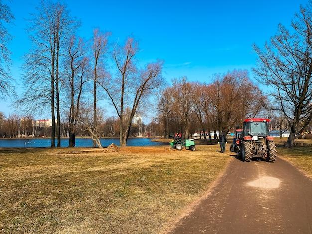 Czerwone ciągniki ciężarówki w parku miejskim wiosna. czyszczenie. wczesna wiosna. pracuje. słoneczny wiosenny dzień.